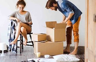 young-couple-moving-in-new-house-unpacking-things-325x210.jpg